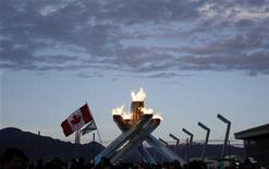 <p>A Canadian flag is seen in front of the Olympic cauldron during celebrations for Canada's victory over the U.S. in the men's ice hockey gold medal game at the Vancouver 2010 Winter Olympics, February 28, 2010. REUTERS/Chris Helgren</p>
