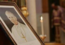 <p>Свеча стоит рядом с портретом Папы Римского Иоанна Павла II в церкви в Рамалле 8 апреля 2005 года. 2 апреля 2005 года на 84 году жизни скончался Папа Римский Иоанн Павел II. REUTERS/Loay Abu Haykel</p>