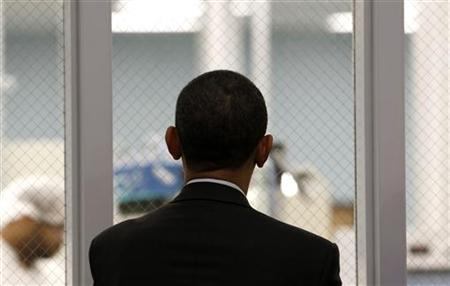 President Obama watches workers through a window as he tours Celgard Inc. in Charlotte, North Carolina, April 2, 2010. REUTERS/Kevin Lamarque