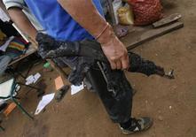<p>Полицейский держит автомат, сгоревший в результате нападения маоистских повстанцев, 16 февраля 2010 года. От 50 до 60 полицейских были убиты во вторник во время атаки маоистских повстанцев в индийском штате Чхаттисгарх, сообщил министр внутренних дел штата. Это нападение стало уже вторым за последние дни и самым кровопролитным за последние годы. REUTERS/Parth Sanyal</p>