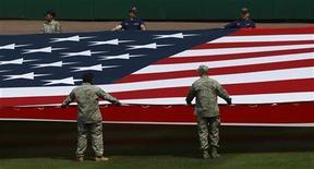 <p>Военные растягивают национальный флаг США в Вашингтоне 5 апреля 2010 года. Администрация президента США Барака Обамы обнародовала во вторник новую доктрину, ограничивающую использование ядерного оружия Соединенными Штатами, запрещающую разработку его новых видов и предвещающую дальнейшее сокращение ядерных арсеналов. REUTERS/Jim Young</p>