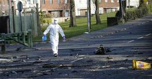<p>Офицер осматривает место взрыва такси около армейских бараков 12 апреля 2010 года. Взрывное устройство, заложенное в угнанном такси, сработало у казарм британской контрразведки MI5 в графстве Даун в Северной Ирландии в понедельник. REUTERS/Cathal McNaughton</p>