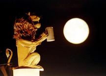 """<p>Скульптура огромного льва, наслаждающегося кружкой пива, """"приветствует"""" восход луны во время Октоберфеста в Мюнхене 20 сентября 1994 года. Залежи льда толщиной по меньшей мере два метра встречаются в маленьких кратерах на Луне, сообщили в понедельник ученые в одном из двух исследований, доказывающих наличие воды на Луне и Марсе. REUTERS/Wolfgang Rattay</p>"""