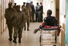 <p>Пациент лежит в коридоре и смотрит на проходящих мимо военных в больнице в Соуэто 12 июня 2007 года. Общественные больницы ЮАР совершенно не готовы к чрезвычайным ситуациям, таким как давка, которые могут возникнуть на предстоящем чемпионате мира по футболу, считает советник ФИФА. REUTERS/Siphiwe Sibeko</p>