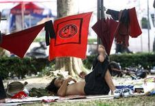 """<p>""""Краснорубашечник"""" отдыхает у баррикад в торговом районе Бангкока 27 апреля 2010 года. Сторонники оппозиции в столице Таиланда Бангкоке парализовали работу метро, а правительство предупредило, что планирует ряд операций по разрешению семинедельного кризиса, в результате которого уже погибли 27 человек. REUTERS/Eric Gaillard</p>"""