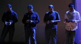 <p>Four men work video game controllers during the Sony E3 2009 press briefing in Los Angeles, June 2, 2009. REUTERS/Fred Prouser</p>