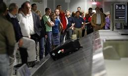 <p>Passengers wait for their luggage in a file photo. REUTERS/Johannes Eisele</p>
