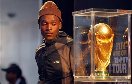 A soccer fan looks at the FIFA Soccer World Cup Trophy in Khayelitsha township near Cape Town, May 7, 2010. REUTERS/Mike Hutchings