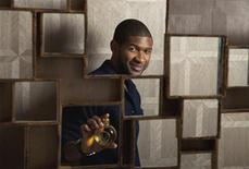 """<p>Singer Usher poses for a portrait with a bottle of his new fragrance """"VIP"""" in New York, December 16, 2009. REUTERS/Lucas Jackson</p>"""