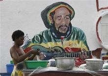 "<p>A resident works in front of a mural of Bob Marley at the ""Rasta Village"" of Port Bouet in Abidjan May 8, 2010. REUTERS/Luc Gnago</p>"