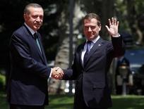 <p>Президент России Дмитрий Медведев пожимает руку премьер-министру Турции Тайипу Эрдогану в Анкаре 12 мая 2010 года. Турция разрешила России без тендера построить первую турецкую атомную электростанцию, возведение которой может обойтись инвесторам примерно в $20 миллиардов, но в обмен они получат станцию в собственность. REUTERS/Umit Bektas</p>