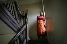 "<p>Forty-seven-year-old Burmese monk U Pyinya Zawta, leader of the ""All Burma Monks Alliance"", a group of exiled monks who fled the protests of the 2007 Saffron Revolution, stands in the stairwell of the makeshift monastery he shares with three others in a small rundown apartment house in the economically depressed upstate New York city of Utica April 27, 2010. REUTERS/Mike Segar</p>"