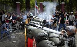 """<p>""""Краснорубашечники"""" на баррикадах возле армейского КПП в Бангкоке 14 мая 2010 года. Армия Таиланда столкнулась с жестким сопротивлением антиправительственных демонстрантов в пятницу при попытке заблокировать место их дислокации. REUTERS/Adrees Latif</p>"""