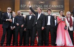 <p>Director Xavier Beauvois (C) and cast members arrive on the red carpet for the screening of the film Des Hommes et des Dieux (Of Gods and Men) in competition at the 63rd Cannes Film Festival May 18, 2010. REUTERS/Jean-Paul Pelissier</p>