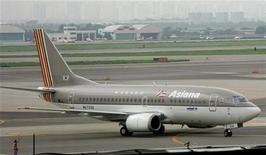<p>Лайнер Asiana Airlines в аэропорту Сеула 17 июля 2005 года. Миллионы пассажиров по всему миру назвали южнокорейскую авиакомпанию Asiana Airlines лучшей в ходе исследования, проведенного британской консультационной компанией Skytrax. REUTERS/Kim Kyung-hoon</p>