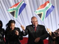 <p>Imagen de archivo del presidente de Sudáfrica, Jacob Zuma, sosteniendo una bandera de su país mientras baila durante el lanzamiento de una campaña en Katlehong. Abr 25 2010. Oficinas y calles de Sudáfrica estaban vestidas de verde y amarillo el viernes al igual que miles de personas, como el presidente Jacob Zuma, como una forma de apoyar a su selección de fútbol que se prepara para disputar la Copa del Mundo. REUTERS/Peter Andrews/ARCHIVO</p>