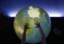 """<p>A visitor places her hands on a """"Tangible Earth"""", a digital globe which real time global metrological data is fed through the Internet from about 300 places in the world, is displayed at an exhibition pavillion inside the media centre for G8 Hokkaido Toyako Summit in Rusustu town, on Japan's northern island of Hokkaido July 6, 2008. REUTERS/Yuriko Nakao</p>"""