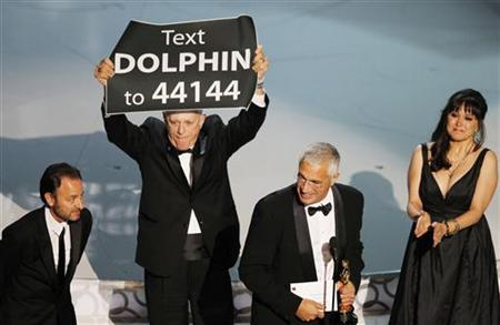 Director Louie Psihoyos (2nd R) accepts an award with producer Fisher Stevens (L), producer Paula DuPre Pesman (R), as cast member Richard O'Barry holds up a sign after ''The Cove'' won best documentary feature during the 82nd Academy Awards in Hollywood March 7, 2010. REUTERS/Gary Hershorn