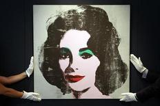 """<p>Employees pose for photographers with the 1963 """"Silver Liz"""" portrait of actress Elizabeth Taylor by late artist Andy Warhol, unseen in over 20 years, at Christie's auction house in London June 8, 2010. Christie's estimates the painting will fetch 6 to 8 million pounds (8.7 to 11.6 million US dollars) at its auction on June 30. REUTERS/Stefan Wermuth</p>"""