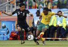 <p>Siphiwe Tshabalala da África do Sul(dir) chuta a bola enquanto o mexicano Ricardo Osorio tenta defender no jogo de abertura da Copa do Mundo no estádio de Soccer City. O Mundial começou nesta sexta-feira com um empolgante empate em 1 x 1 entre África do Sul e México. 11/06/2010 REUTERS/Eddie Keogh</p>