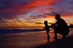 <p>A man plays with his son during sunrise at Kailua Beach in Kailua, Hawaii in this file photo. REUTERS/Lucy Pemoni</p>