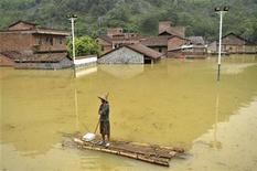 <p>Мужчина стоит на самодельном плоту на окраине поселка Синьчэн в Гуанси-Чжуанском автономном районе, КНР 4 июня 2010 года. Проливные дожди на юге Китая стали причиной гибели по меньшей мере 175 человек, еще 107 пропали без вести. REUTERS/Stringer</p>