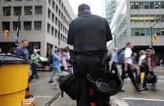 <p>A police officer stands guard as people cross the street ahead of the G20 summit in Toronto, June 22, 2010. REUTERS/Mark Blinch.</p>