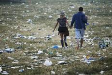 <p>A couple hold hands as they walk through litter at dawn in the field in front of the Pyramid Stage at the Glastonbury Festival 2010 in south west England June 26, 2010. REUTERS/Luke MacGregor</p>