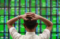 <p>A man looks at a display board showing stock market prices inside a brokerage in Taipei May 25, 2010. REUTERS/Nicky Loh</p>