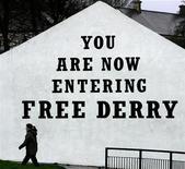 <p>A woman walks past 'Free Derry Corner' in the Bogside area of Londonderry, Northern Ireland, November 22, 2004. REUTERS/Paul McErlane</p>