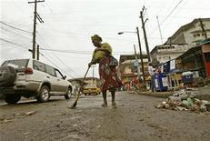 <p>A file photo of a woman sweeping a road along Carey Street in Monrovia November 21, 2005. REUTERS/OLD</p>