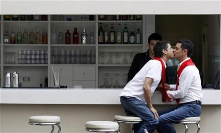 Jose Maria Di Bello (R) and his partner Alex Freyre kiss at a hotel bar after an interview with Reuters in Buenos Aires November 25, 2009. Freyre and Di Bello, Latin America's first same-sex couple to be granted a marriage license, hope their wedding will pave the way for other homosexual couples in Argentina to marry. REUTERS/Marcos Brindicci