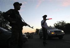 <p>Офицер киргизской полиции и вооруженный военнослужащий патрулируют дорогу в Бишкеке, 26 июня 2010 года. Власти Киргизии задержали одного из братьев свергнутого президента, обвиняемого в организации кровавых межэтнических столкновений на юге страны в июне, повлекших сотни жертв. REUTERS/Vladimir Pirogov</p>