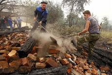 <p>Rescue personnel remove the debris of a burnt out house in the village of Borkovka, outside the town of Vyksa, some 150 km (93 miles) southwest of the Volga city of Nizhny Novgorod, July 31, 2010. Raging wildfires spread across parts of western Russia on Saturday, engulfing 30 percent more land in just 24 hours, and Prime Minister Vladimir Putin described the situation as very difficult. REUTERS/Mikhail Voskresensky</p>