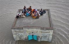 <p>A family takes refuge on top of a mosque while awaiting rescue from flood waters in Sanawa, a town located in the Muzaffar Ghar district of Pakistan's Punjab province August 5, 2010. REUTERS/Stringer</p>