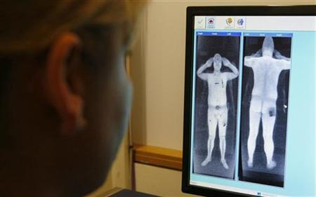 A security officer examines a computer screen showing a scan from a RapiScan full-body scanner, being trialled by Manchester Airport, during a photocall at the airport, in Manchester, northern England January 7, 2010. REUTERS/Phil Noble
