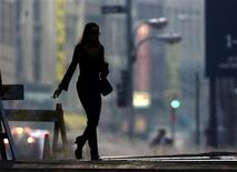 <p>A woman walks across a street in New York's Financial district in a file photo. REUTERS/Russell Boyce</p>