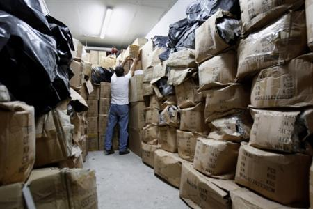 An employee of Greece's Financial and Economic Crimes Unit performs a search amongst confiscated boxes inside a warehouse in Athens July 23, 2010. Greece has vowed to go after tax dodgers and end what the IMF has called ''wide tax evasion and corruption'' as part of its 110 billion euro ($143 billion) rescue deal with the European Union and the International Monetary Fund (IMF). REUTERS/John Kolesidis