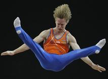 <p>Epke Zonderland of the Netherlands competes on the Parallel Bars during the men's final round of the Doha Gymnastics World Cup at the Aspire Academy in Qatar March 24, 2010. REUTERS/stringer</p>