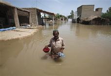 <p>Ali Hassan, a villager, holds his sandals and meal as he wades through floodwaters in Amri village, August 19, 2010. REUTERS/Akhtar Soomro</p>