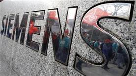 <p>Foto de archivo en la que los trabajadores del grupo Siemens se reflejan en el logo de la compañía en Berlín. Nov 26, 2009. REUTERS/Tobias Schwarz</p>