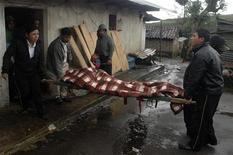 <p>Люди выносят тело человека, погибшего в одной из провинций Гватемалы в результате оползней, 5 сентября 2010 года. Еще как минимум 22 человека, пытавшихся откопать ранее заваленный оползнем автобус, погибли в результате схода повторной сели в Гватемале в воскресенье, доведя число жертв стихии до 41 человека. REUTERS/Doriam Morales</p>