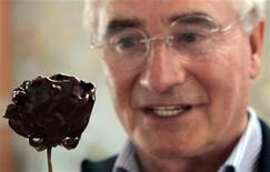 <p>Roberto Nevado looks at a deep chocolate rose at his flower plantation in Pujili, south of Quito August 27, 2010. REUTERS/Guillermo Granja</p>