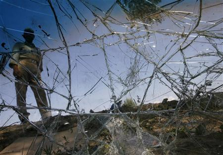 An Indian policeman is seen through the windshield of an Indian police vehicle, damaged by protesters in a clash, in Srinagar September 16, 2010. A wave of disappointment swept across curfewed Indian Kashmir on Thursday after no concrete results emerged out of a key meeting aimed at ending spiralling protests that are the worst in recent times. REUTERS/Danish Ismail