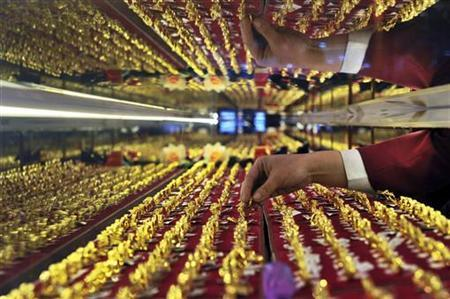 A vendor arranges gold rings on display at a jewelry shop in Shenyang, Liaoning province March 9, 2010. . REUTERS/Sheng Li