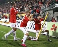 <p>O jogador Lewis Holtby (centro) comemora com companheiros gol do Mainz contra o Cologne pelo Campeonato Alemão. REUTERS/Kai Pfaffenbach</p>