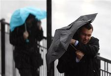 <p>Commuters struggle through heavy rain and strong winds across London Bridge to the city of London in this March 10, 2008 file photo. REUTERS/Stephen Hird</p>