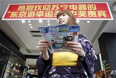 """<p>A woman clad in a yukata, or a casual summer kimono, hands out flyers to tourists at a duty-free retail store at Tokyo's Akihabara district July 1, 2010. The sign reads, """"Welcome Suning Electronics' Tokyo lucky draw winners"""". REUTERS/Issei Kato</p>"""