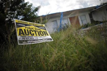 An auction sign for a property is seen at the front garden of a foreclosed house in Miami Gardens, Florida in this September 15, 2009 file photo. REUTERS/Carlos Barria/Files