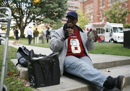 Homeless shelter resident Richard Paul, who used to be a construction worker, explains his recent leg surgery while sitting in a park as people wait in line to purchase pizza from a pizza mobile in Washington, October 21, 2010. REUTERS/Molly Riley